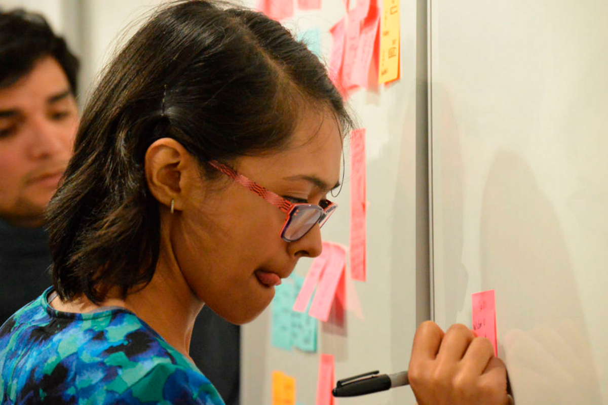 A student brainstorms with her classmates as part of a Design Strategies class taught onsite at IBM's design studios in Austin. Photo by Alicia Dietrich.