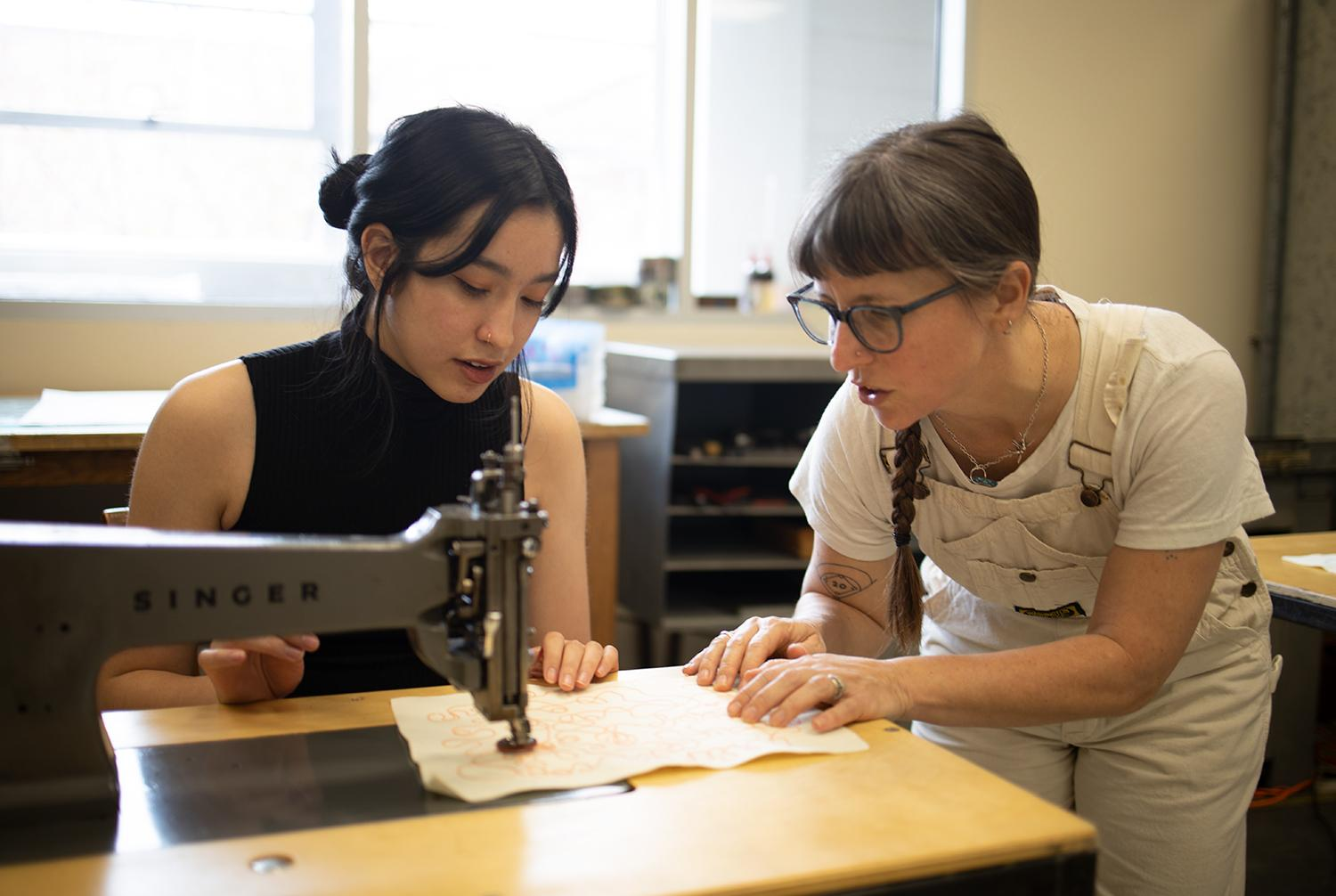 Kathie Sever teaches Design junior Hue Minh Cao how to chain stitch during the workshop