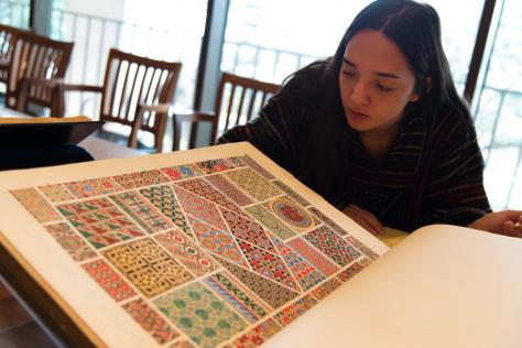 Emily Park is looking at the folio edition of Owen Jones's Grammar of Ornament (London, Day and Son, 1856). Photograph by Derek Rankins. Courtesy Harry Ransom Center.