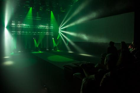 green concert lighting with a small crowd to the right