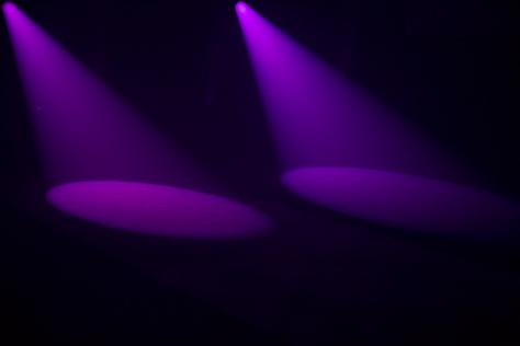 two purple spotlights create cone shapes on the floor
