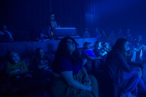 students are bathed in blue light as they watch a concert light show