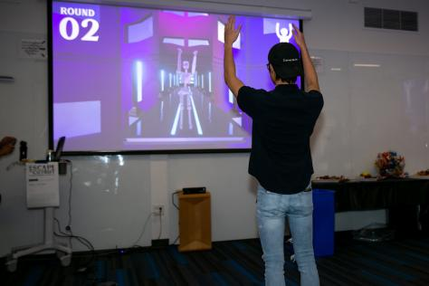 Showcase attendee plays interactive student video game