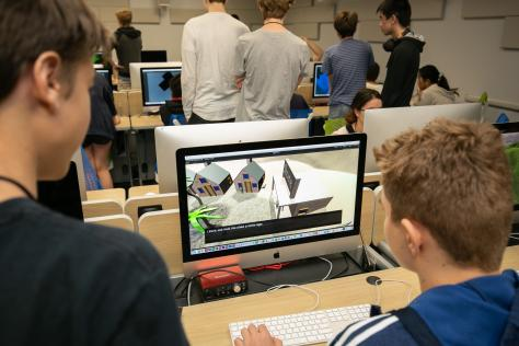 two high school students play a video game they designed on a desktop computer at SDCT's 2019 Game Design Summer Institute at UT Austin