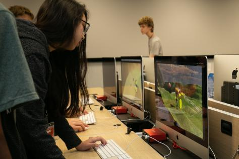 a high school student leans over a computer to play a video game created at the 2019 SDCTx Game Design Summer Institute at the University of Texas at Austin