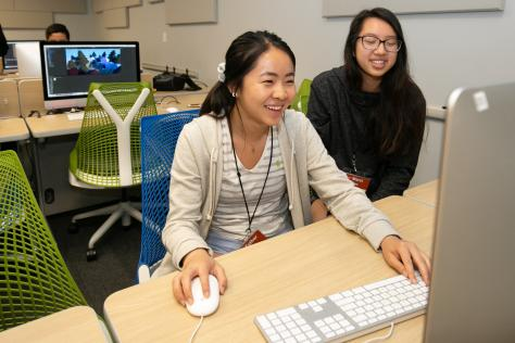two high school students smile and laugh as they play a video game they created at the 2019 SDCTx Game Design Summer Institute