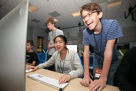 a high school student leans over a computer and laughs as he watches another student play their original video game created at the 2019 SDCTx Game Design Summer Institute