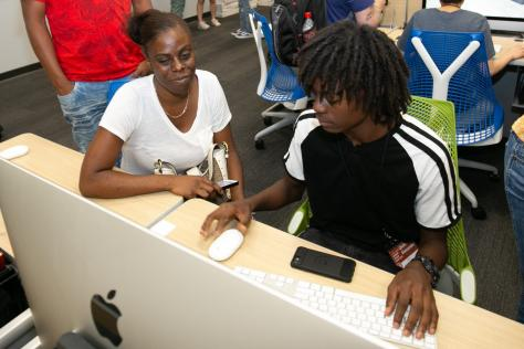 a high school student demonstrates their original video game to their mother at the 2019 SDCTx Game Design Summer Institute