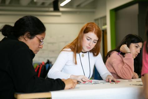 High school student with long red hair arranges small objects to make a physical typeface at the 2019 Graphic Design Summer Institute at UT Austin
