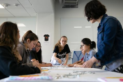 A high school student reaches for an object on a long table. A group of students is seated around her as they work on a physical typeface made of uncommon objects at the 2019 Graphic Design Summer Institute at UT Austin