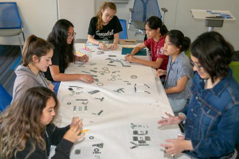 7 high school students are seated around a long table as they work to create a physical typeface with small metal objects at the 2019 SDCTx Graphic Design Summer Institute at UT Austin