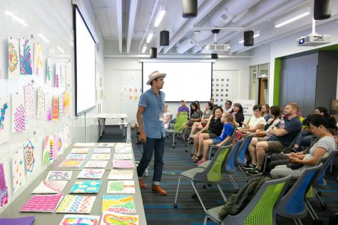 UT Austin design faculty Jason Wilkins stands in the center of a classroom as he speaks to parents at the 2019 SDCTx Graphic Design Summer Institute showcase
