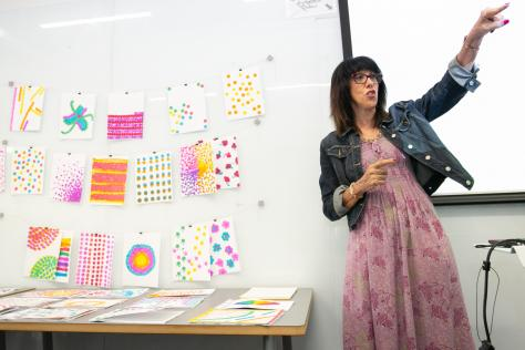 School of Design and Creative Technologies Assistant Dean Doreen Lorenzo standing next to work created by high school students at the 2019 SDCTx Graphic Design Summer Institute at UT Austin