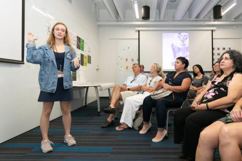 a high school students stands at the front of a classroom full of parents as they present their work from the 2019 SDCTx Graphic Design Summer Institute at UT Austin