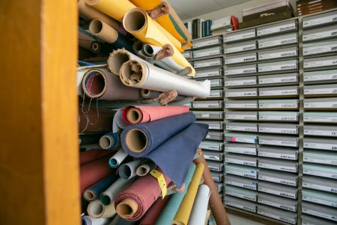 Colorful fabric rolls stacked next to the Rob Roy Kelly Collection in the Design Lab at UT Austin
