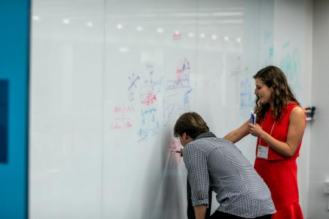 Two Design + Impact attendees draw a diagram on a white board at the School of Design and Creative Technologies