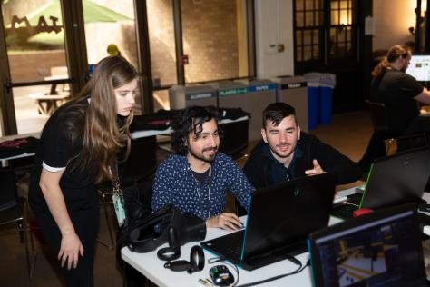 three game designers gather around a computer while they design augmented reality for the VR Austin Game Jam 2019