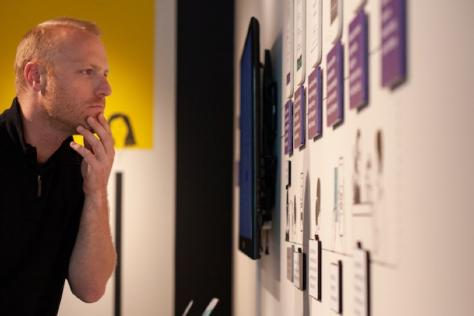 A man examines one of the exhibitions at Work for Progress