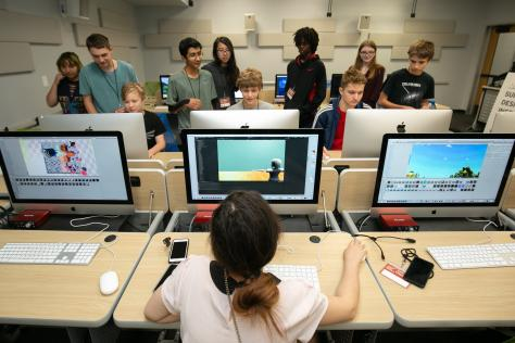 students playing games they designed on computers at 2019 game design summer camp