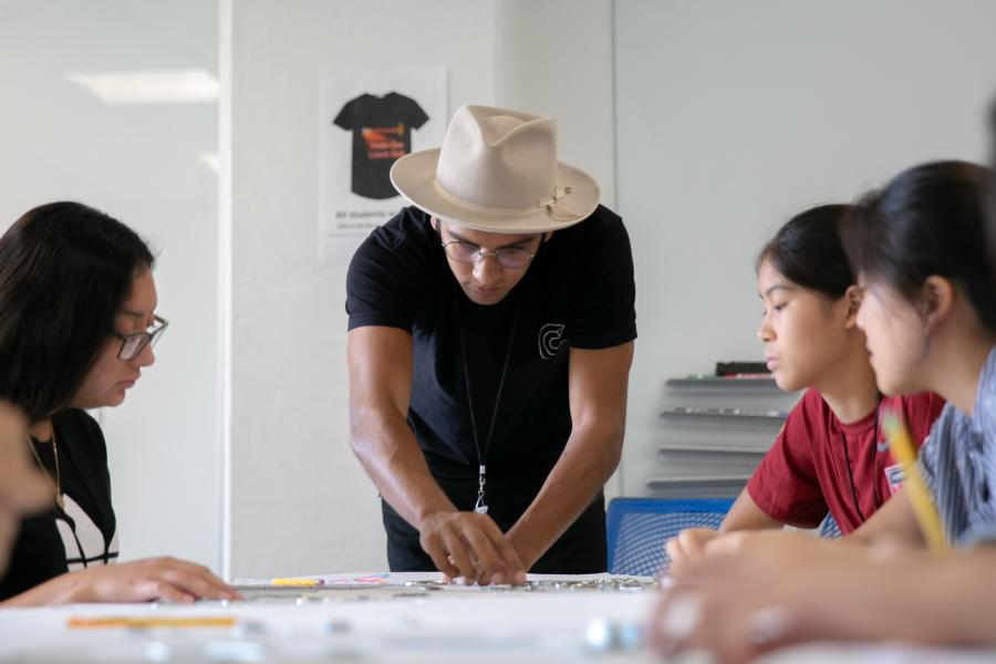 UT Austin design faculty Jason Wilkins helps high school students create a physical typeface from small metal objects at the 2019 SDCTx Graphic Design Summer Institute