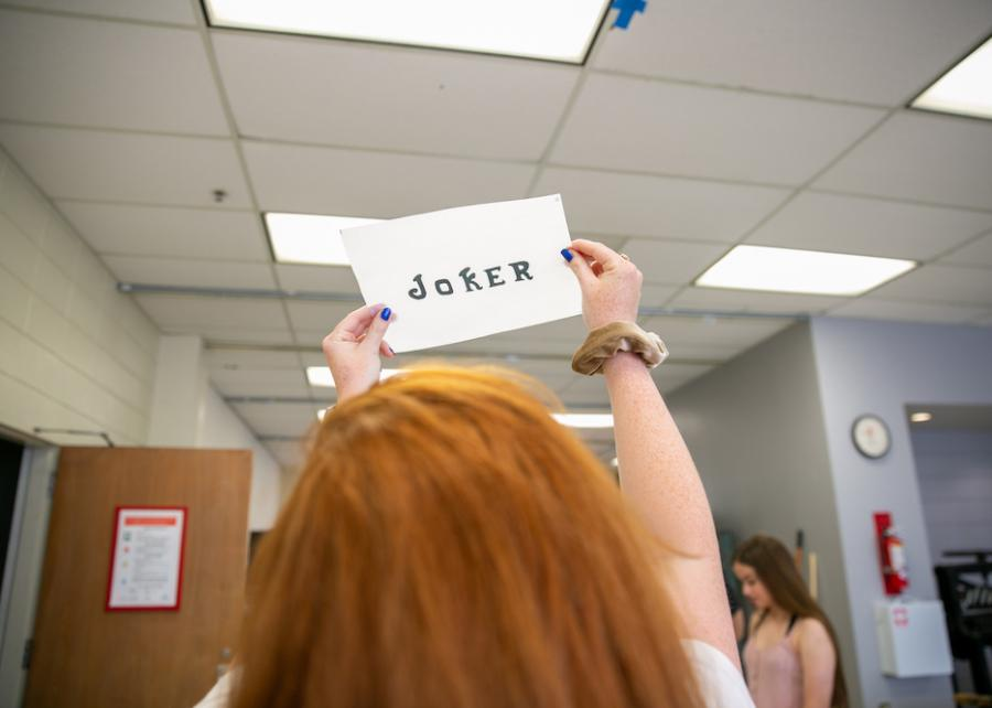 "undergraduate design student holding up card with the word ""joker"" letterpress printed on it in the Design Lab at UT Austin"