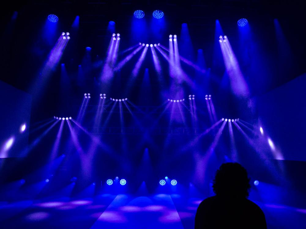 blue concert lighting with a person's silhouette in the forefront