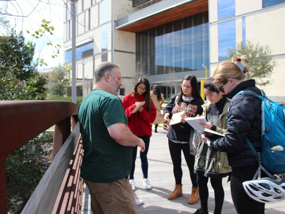 Design students stand on a bridge outside and take notes as they study the creek below them and their professor lectures