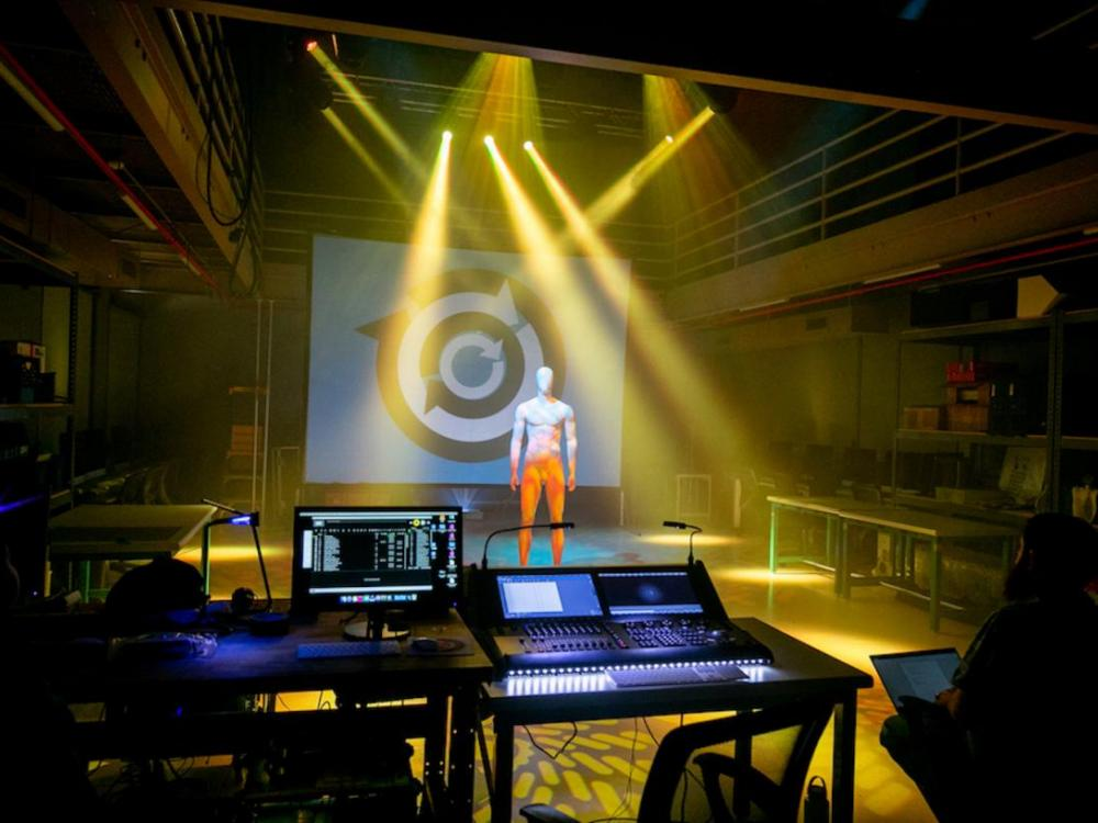 still of light show presentation from professor Matt Smith's live event engineering class. a mannequin stands in the middle of the PLAI lab while the light show happens around you
