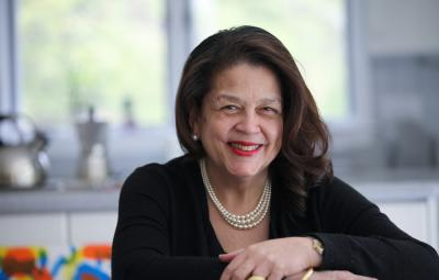 Photo of Cheryl Miller leaning forward and smiling in her office. The background has been blurred out.