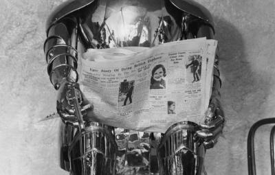 black and white photo of tin man sculpture reading a newspaper