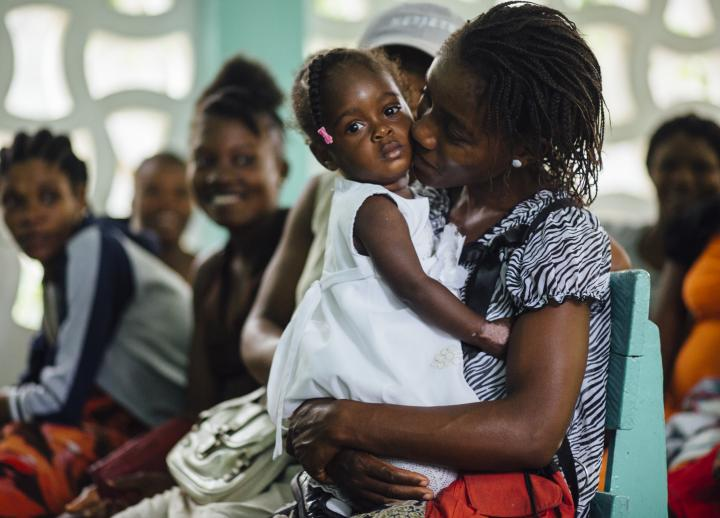 a Haitian mother holds her young daughter, who wears a white dress and is looking directly into the camera