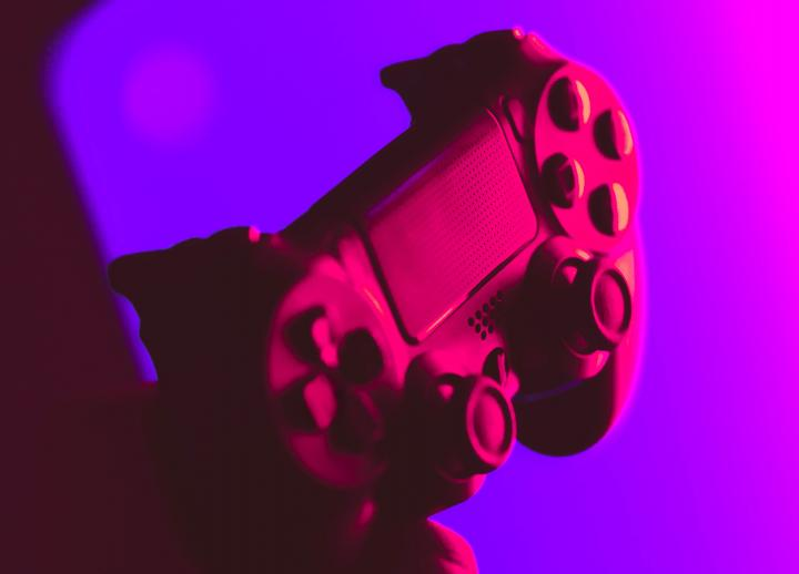 close up of handheld video game controller in purple lighting