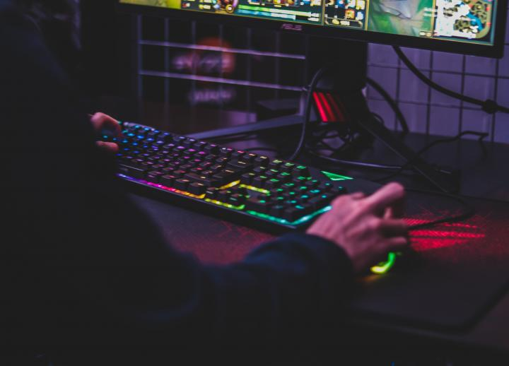 hands typing on a computer and moving a mouse. the keys on the keyboard are backlit by rainbow LED lights