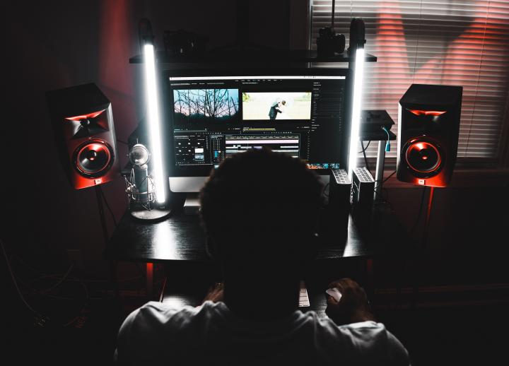 a student sits at a desk with speakers and a desktop computer to work on music in their home studio