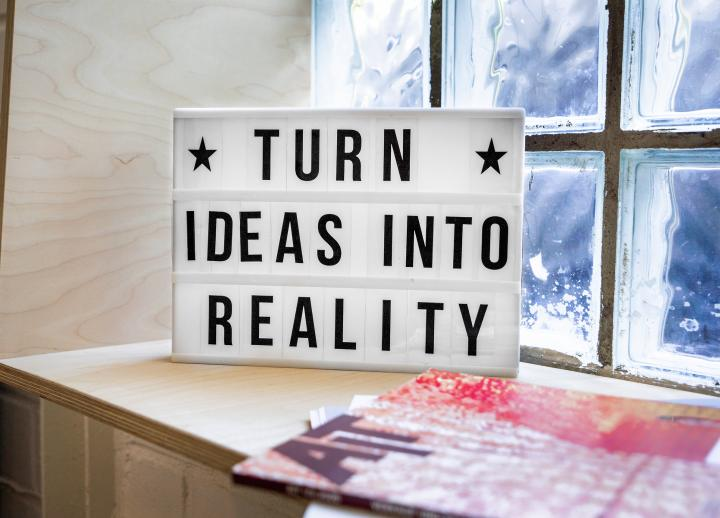 "marquee sign in window sill reads ""Turn Ideas Into Reality"""