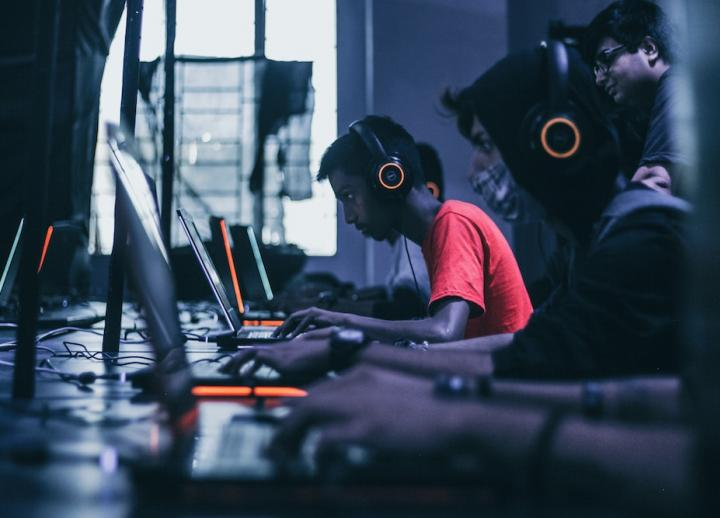 People playing video games on their laptops with headsets (Photo by Fredrick Tendong on Unsplash)