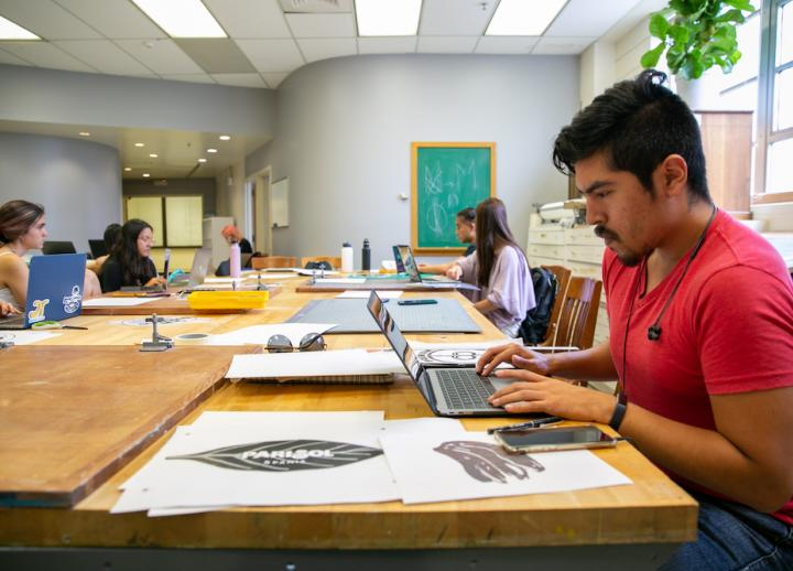 design student works on a project on laptop in the Design Lab