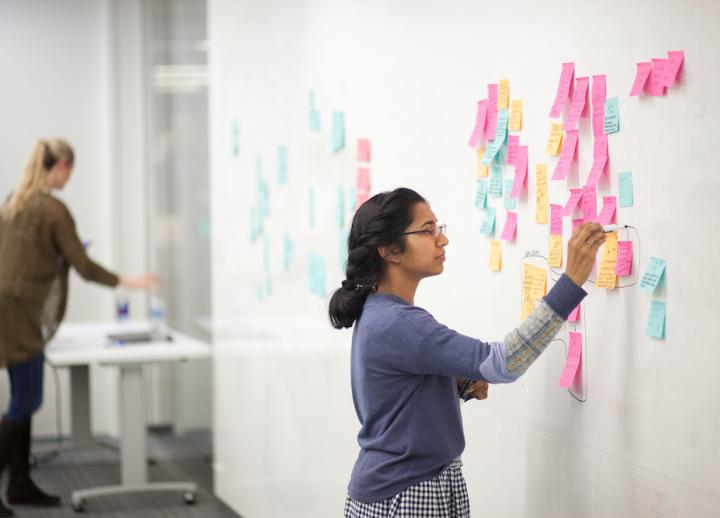 An undergraduate UT Austin design student organizes their thoughts using sticky notes on a white board