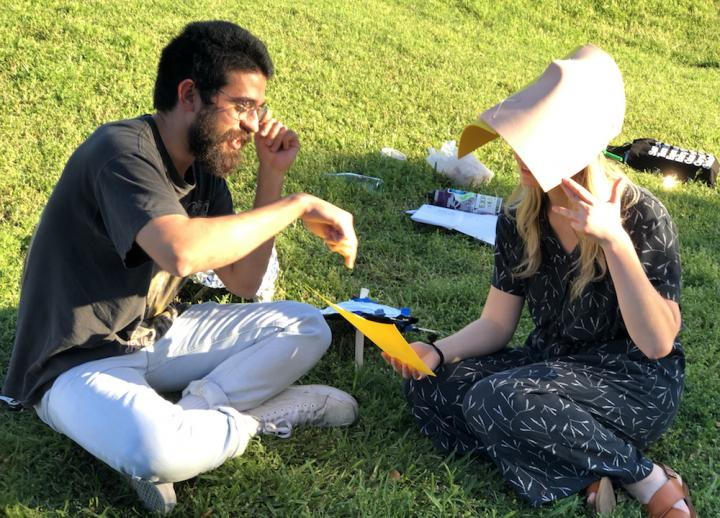 two undergraduate students sit on grass and study a piece of paper. the student on the left points to the paper, and the student on the right wears a paper head covering