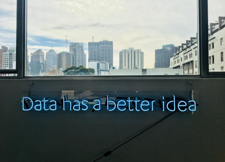 "Blue neon sign reading ""data has a better idea"" sits beneath a window looking out onto a city skyline"