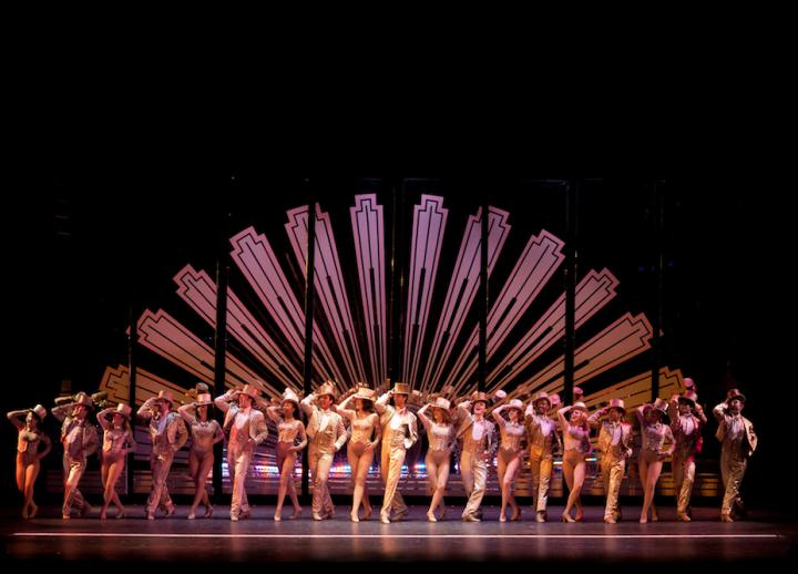 a chorus line of dancers in suits and top hats posing onstage with a large fan backdrop