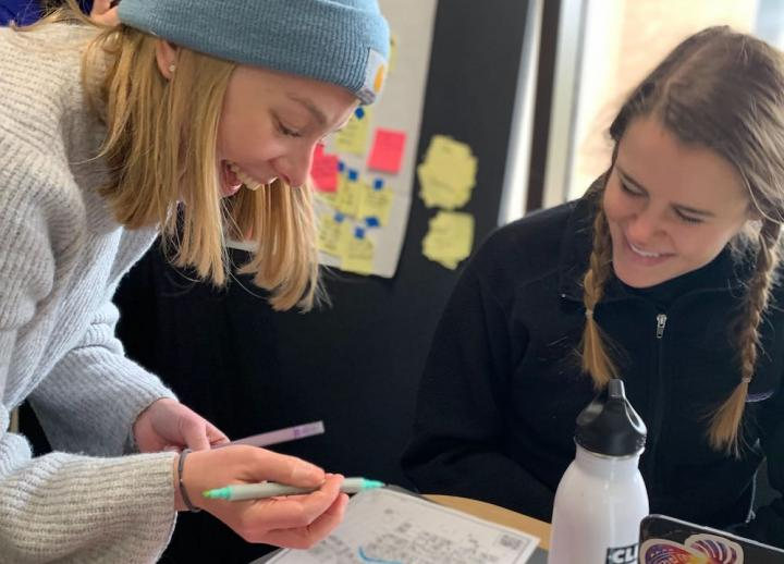 two students laugh as they make notes on a map together