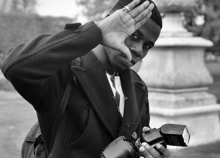 man holding a camera with his hand up to his eye using his thumb to frame the shot