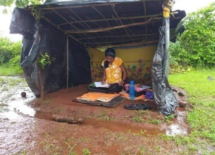 a young woman studying to be a doctor in a shed made of tarps with a dirt floor. It has been raining, so she is surrounded by mud