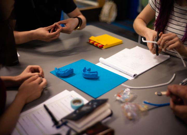 Four students working on 3-D models at a table. Faces are not visible, only hands working with models
