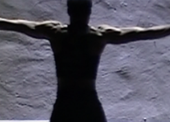 African American man with arms outstretched facing a rock wall with back to camera
