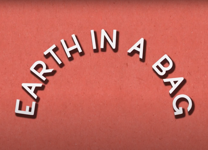 "Red title slide with off-white text that reads ""Earth in a Bag."" words are curved like a rainbow"