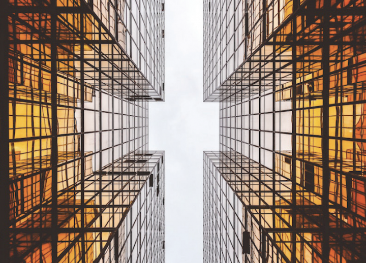 two tall buildings made of windows from the perspective of someone standing between them looking up to the sky