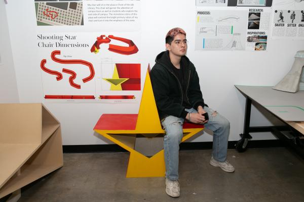 student sits on star-shaped chair designed for Objects and Spaces classes