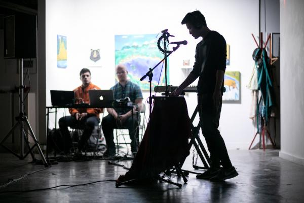 Wide shot of student performing in the foreground while instructors observe in the background